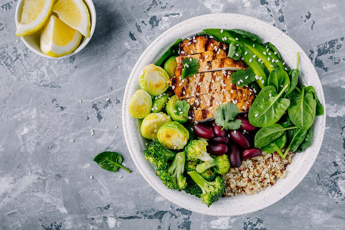 Healthy-buddha-bowl-with-grilled-vegan-chicken-quinoa-spinach-avocado-sprouts-broccoli-red-beans-with-sesame-seeds